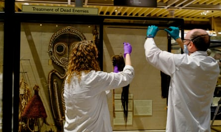 Staff remove the shrunken heads, or tsantsas, from Peru and Ecuador, from the 'Treatment of Dead Enemies' cabinet.