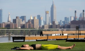 A woman lies in Domino Park during a heatwave in New York, US
