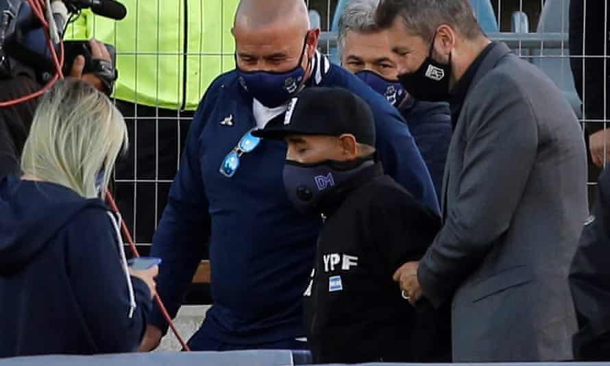 Diego Maradona is helped onto the pitch before Gimnasia y Esgrima's game at the Estadio Juan Carlos Zerillo on Friday, on his 60th birthday.