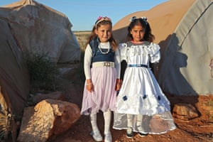 Girls wear holiday dresses for Eid in the Tah camp for internally displaced persons in Syria's rebel-held north-western province