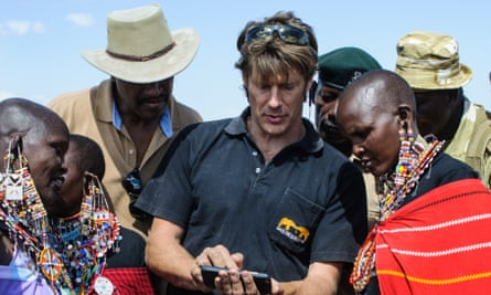 Frank Pope of Save The Elephants explains to Maasai women how a mobile phone is used to see the location of an elephant fitted with a tracking collar, in Amboseli National Park, Kenya, 10 September 2016.