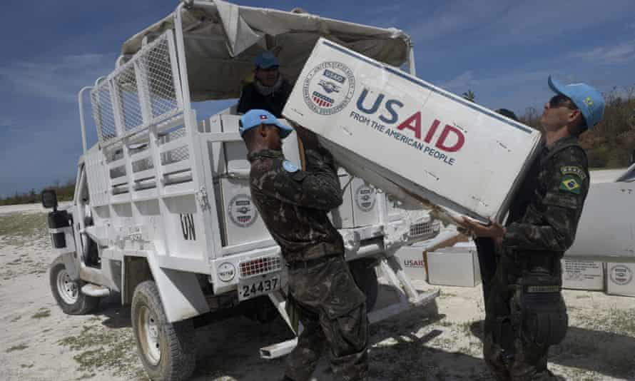UN blue helmets load aid which arrived in US helicopters onto a truck for people affected by Hurricane Matthew, in Jeremie, southwest of Port-au-Prince, Haiti