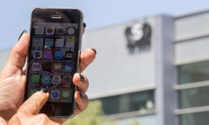 A woman uses her smartphone in front of the NSO Group offices in Herzliya, near Tel Aviv