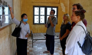 A tour guide shows tourists around the recently reopened Tuol Sleng genocide museum in Phnom Penh