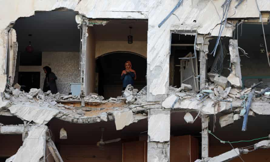 Palestinian women inspect the rubble of a building following an Israeli airstrike on Gaza City.
