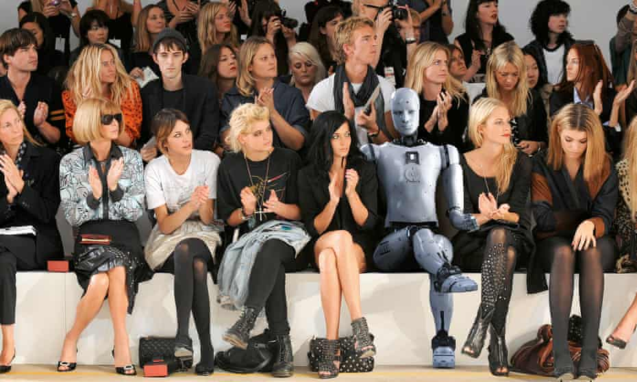 A robot sits in the audience on the side of the catwalk