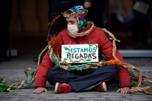 Madrid, Spain. An activist from Extinction Rebellion sits outside the Agriculture Ministry wearing a sign that reads We Are Glued, after sticking their hands to the pavement during a protest demanding the Spanish government protect biodiversity