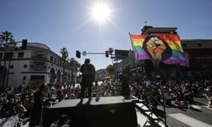 A speaker addresses the crowd from a stage on Sunset Boulevard .