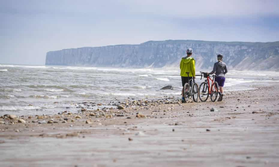Two figures with bikes on an empty sandy Yorkshire beach, standing near the sea, a slightly stormy sky