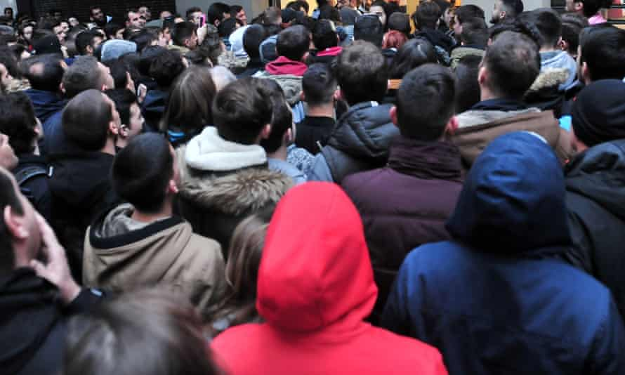 People wait outside of a department store in Thessaloniki on 25 November, 2016. Long queues snaked outside department stores and roads were blocked near malls thousands of Greeks bucked falling wages and joblessness to join the country's first-ever Black Friday shopping craze. In Athens, Thessaloniki and other major Greek cities, the queues formed before participating stores -- mostly tech and clothes chains-- opened at 0600 GMT. It was soon clear that most of the shoppers were youngsters skipping school to take advantage of up to 80-percent reductions in the sales. / AFP PHOTO / SAKIS MITROLIDISSAKIS MITROLIDIS/AFP/Getty Images