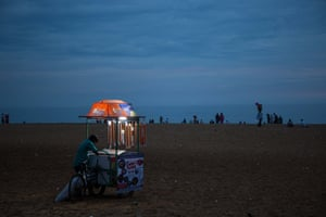 Photographer Laura O'Brien: I was walking along Kollam Beach in Kerala when I saw this lonely ice-cream seller still  searching for customers in the dusk. As the daylight was fading, the light in his little kiosk burned bravely but no one was buying.