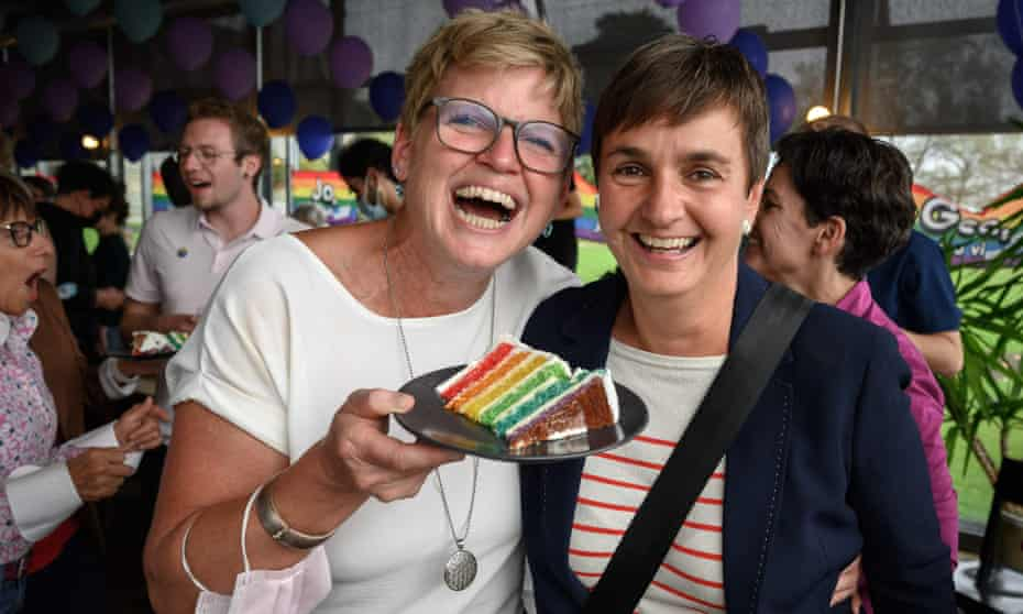 A couple pose with a slice of wedding cake at an event following the referendum on same-sex marriage, Bern, Switzerland.