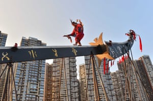 Guiyang, China. A performer walks barefoot along a giant knife during a celebration of the founding of the People's Republic of China