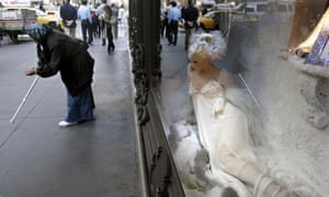 A woman begs outside Saks Fifth Avenue, New York City.