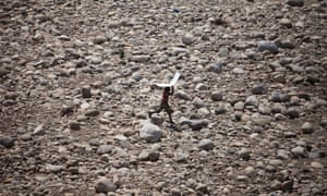A small boy protects himself from the sun as he walks on a dried-up riverbed in Jammu, India. The country experienced record temperatures in May.