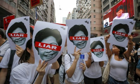 Protesters hold pictures of Carrie Lam as they march in Hong Kong