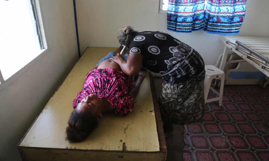 Healthcare worker Jacinta conducts an antenatal examination; the bed does not have a mattress.