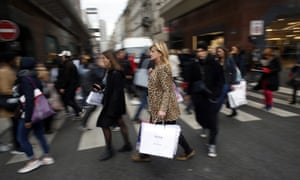 Crowds on pedestrian crossing, one woman in focus carrying Boss shopping bag