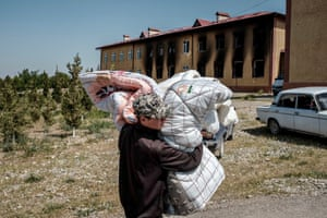 Maksat, Kyrgyzstan. A man carries belongings through the village near the border with Tajikistan after border clashes left at least 34 Kyrgyz citizens dead