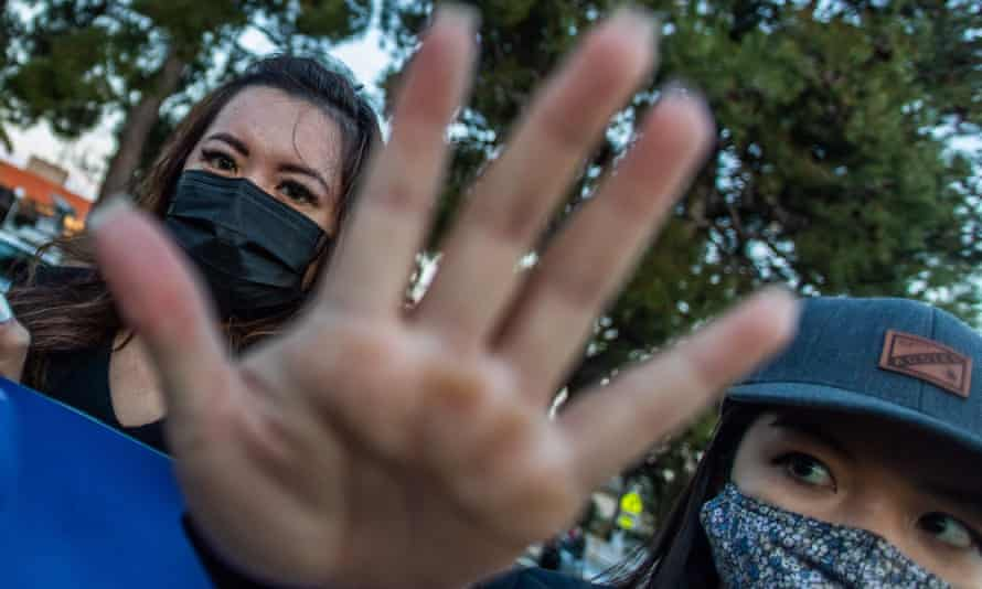 Clover and Julie Tran stand with outstretched hands during a candlelight vigil in Garden Grove, California, after the shootings that left eight people dead in Atlanta, Georgia, including at least six Asian women.