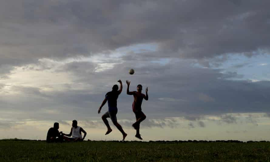 Young men play a game of rugby at sunset in Nuku'alofa, Tonga. The largest cluster of places without the coronavirus can be found in the scattered islands of the South Pacific