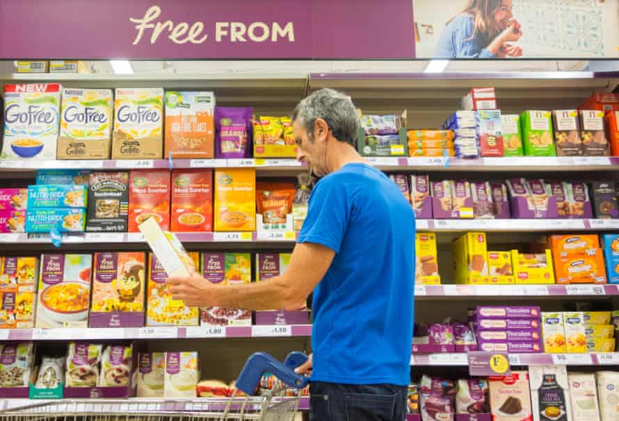 Man reading label on gluten-free products in Tesco supermarket.