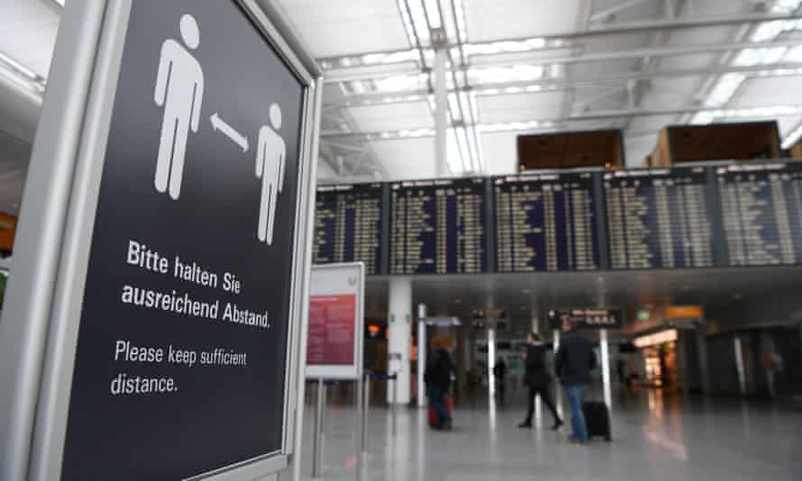 a sign at a German airport tells passengers to keep their distance from other people
