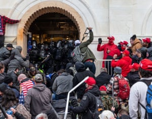 Washington DC, US. Rioters clash with police trying to enter Capitol building through the front doors. Rioters broke windows and breached the Capitol building in an attempt to overthrow the results of the 2020 election. Metal bars and tear gas were used