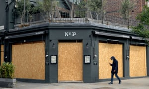 A man with a face mask passes a boarded-up bar in Clapham, south London.
