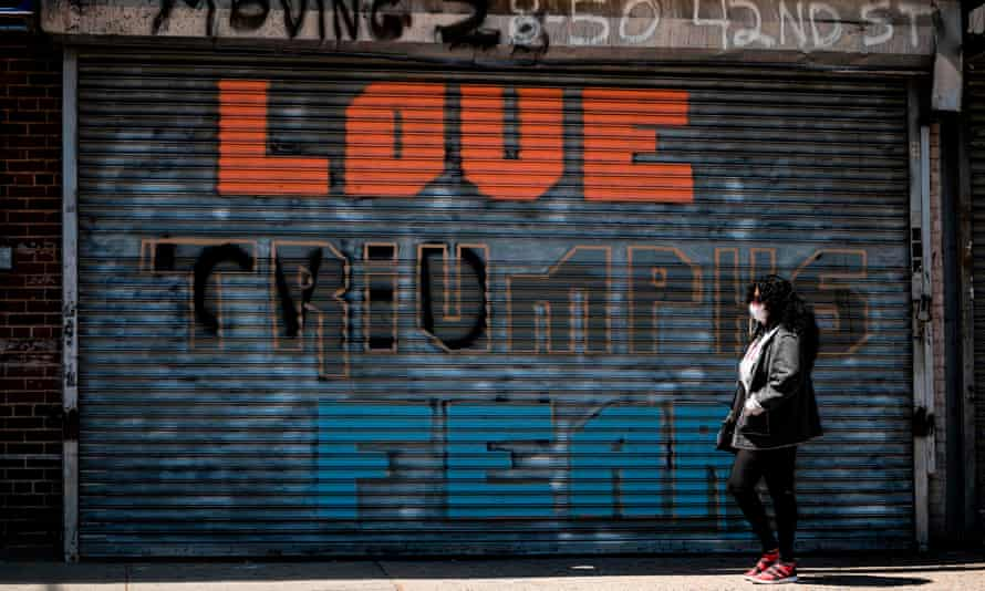"""A woman wearing a facemask walks past a shuttered shop reading """"love triumphs fear"""" amid the coronavirus pandemic in Queens, New York City"""