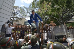 Opposition leader Juan Guaido attempts to climb the gates to enter the compound of the national assembly, after he and other opposition lawmakers were blocked by police from entering a session to elect a new assembly in Caracas.