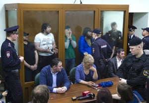 Security forces stand guard as Khamzat Bakhayev, Temirlan Eskerkhanov, Shadid Gubashev, Anzor Gubashev and Zaur Dadayev, who have been convicted of the contract killing of opposition leader Boris Nemtsov, stand inside a glass cage for sentencing in Moscow.