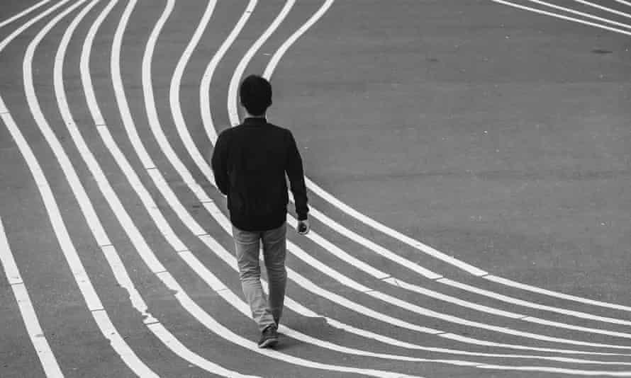 Rear view of man walking along famous Superkilen Park in Copenhagen, DenmarkClose-up back view of Man walking along famous Superkilen Park, a modern public park and urban open space in the Nørrebro district, landmark of Copenhagen, capital city of Denmark.