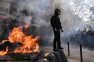 A masked protester stands next to a burning barricade during May Day demonstration in Paris.