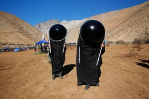 Chileans watch the sky with special suits prior to a total solar eclipse in Paiguano, Chile.
