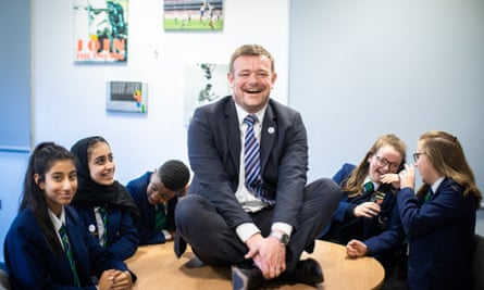 Head James Haseldine sitting on a table surrounded by pupils