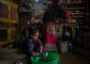 Girl squatting on floor rinsing pot as grandmother works