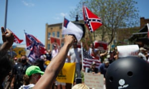 Anti-racist protesters raise fists towards supporters of the Confederacy at the Alamance county courthouse at at a rally in Graham, North Carolina, on 11 July.