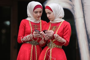 Grozny, ChechnyaTwo girls wearing traditional costume during celebrations marking the Day of the Chechen Language compare smartphones.