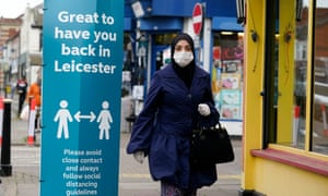 A woman wearing a face mask walking past social distance advisory signs in Leicester's North Evington neighbourhood today.