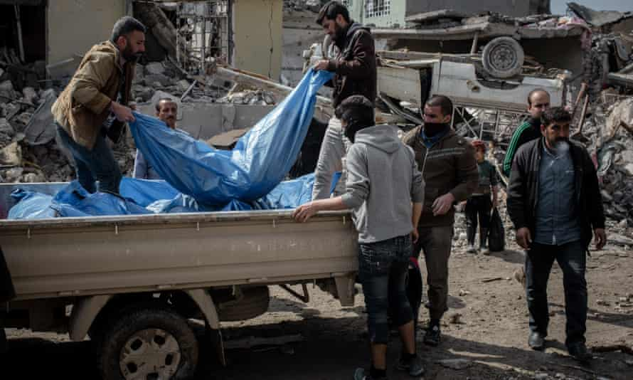 Men load the bodies of people recovered from the rubble of a house in western Mosul.