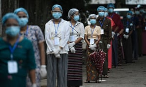 People wearing face shields, masks and rubber gloves to halt the spread of Covid-19 coronavirus wait to vote at a polling station in Yangon on November 8, 2020.