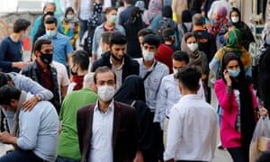 Iranians wearing face masks walk through a market in Tehran, Iran