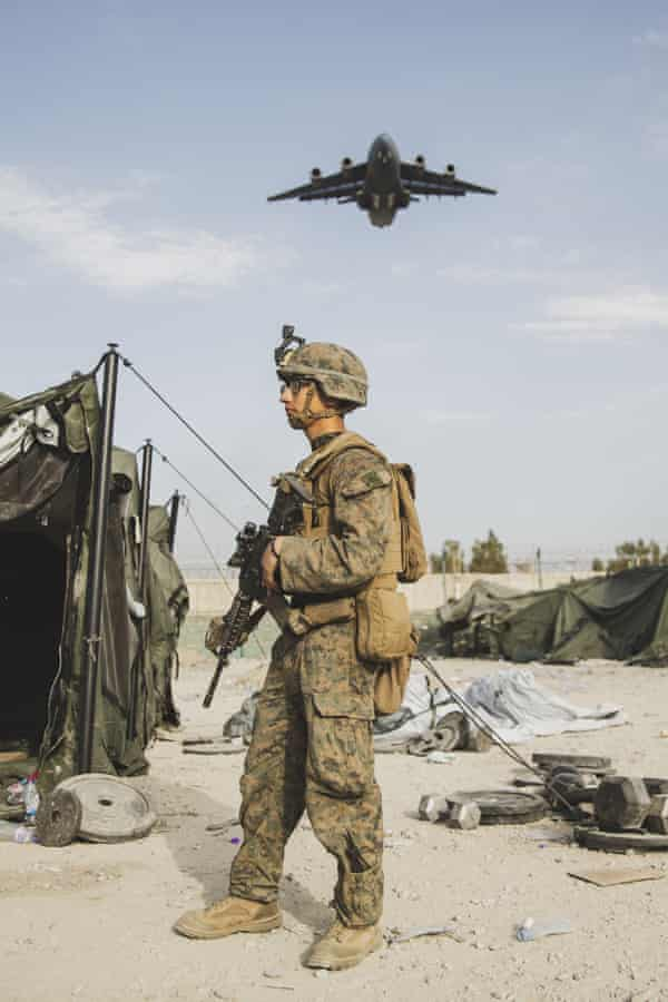 In this image provided by the US.Marine Corps, a US marine provides security assistance during an evacuation at Kabul airport.