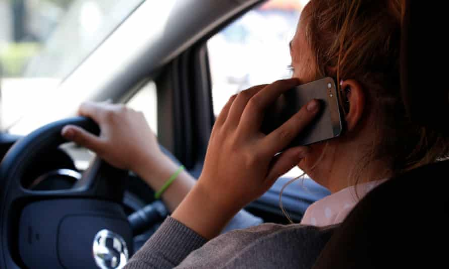 A person drives while holding a mobile phone