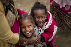 Two displaced Tigrayan girls laugh next to their mother outside the Hadnet General secondary school which has become a makeshift home to thousands displaced by the conflict in Mekele in the Tigray region of northern Ethiopia.