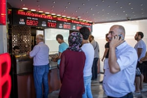 People line up to exchange money at a currency exchange office in Istanbul, Turkey