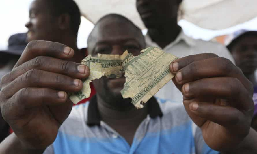 Albert Marombe holds up a tattered $20 bill