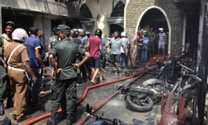 Locals and police gather at a church in Colombo after an explosion
