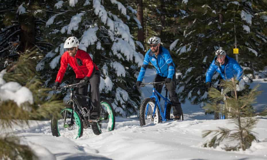 A trio of male riders in the snow on fatbikes: bicycles with extra wide, ridged tyres for cycling in extreme weather conditions.